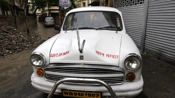 An Indian government owned Ambassador car is parked beside a road in Kolkata, india, Monday, May 26, 2014. India's oldest car factory has abruptly suspended production of the hulking Ambassador sedan that has a nearly seven-decade history as the car of the Indian elite. (AP Photo/ Bikas Das)