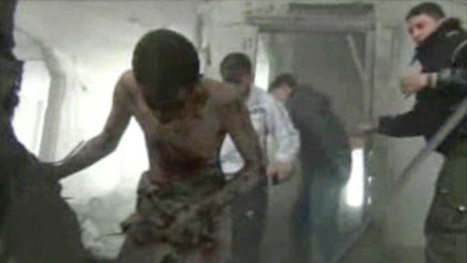 In this image taken from video obtained from Bambuser, which has been authenticated based on its contents and other AP reporting, men help an injured and heavily bleeding man out of a building that was destroyed following what activists said were two airstrikes in the Arbeen neighborhood of Damascus, Syria, Friday, Jan. 25, 2013. (AP Photo/Bambuser via AP video)