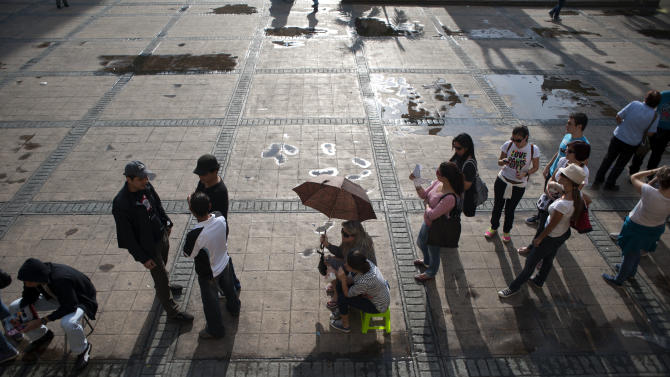 CORRECTS LOCATION TO CANDELARIA SQUARE  IN DOWNTOWN CARACAS.- Voters line up at a polling station during the presidential election at Candelaria square in downtown Caracas, Venezuela, Sunday, Oct. 7, 2012.  President Hugo Chavez is running for re-election against opposition candidate Henrique Capriles. (AP Photo/Sharon Steinmann)