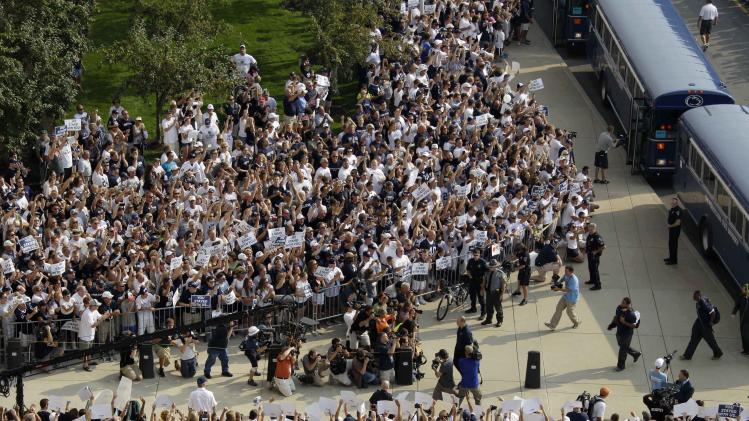 Penn State football fans surround the Penn State football team buses as Penn State head coach Bill O'Brien, center, leads his team into Beaver Stadium for their season opener against Ohio in State College, Pa., Saturday, Sept. 1, 2012. (AP Photo/Gene J. Puskar)