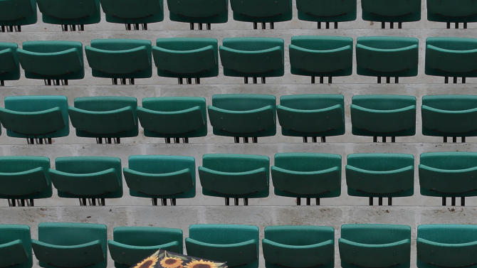 A spectator sits under an umbrella on center court as matches were delayed because of the rain for the French Open tennis tournament at the Roland Garros stadium Tuesday, May 28, 2013 in Paris. (AP Photo/Christophe Ena)