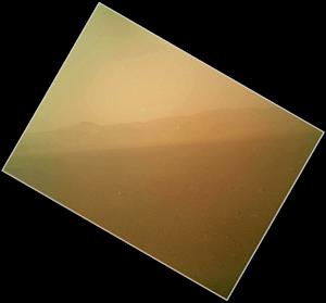This image released on Tuesday Aug. 7,2012 by NASA shows the first color view of the north wall and rim of Gale Crater where NASA's rover Curiosity landed Sunday night. The picture was taken by the rover's camera at the end of its stowed robotic arm and appears fuzzy because of dust on the camera's cover. (AP Photo/NASA)