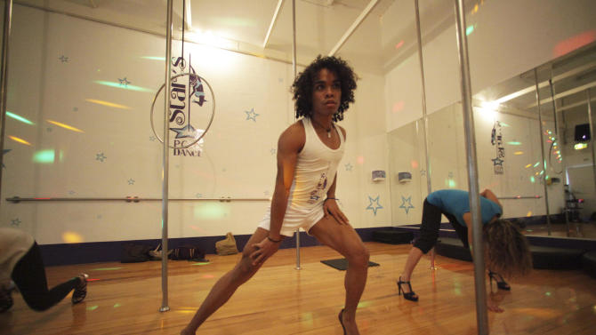 In this photo taken July 13, 2012, Grey Betancourt, center, teaches sensual expression and pole dancing inside a pole dancing studio at a gym in Caracas, Venezuela. Pole dancing may have started out in strip clubs, but since the 1990s, it's become an all-ages exercise and sport phenomenon the world over. Now, it's hit the streets in Venezuela, a country that's made beauty and fitness a cult and minted more Miss Universes than any other except the United States. (AP Photo/Fernando Llano)