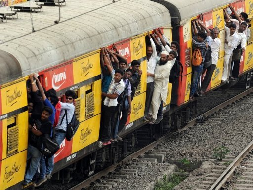 Commuters hang onto an overcrowded suburbun railway train on the Central Railway (CR) line in Mumbai on April 19, 2012