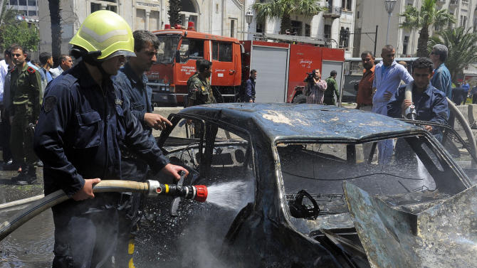 In this photo released by the Syrian official news agency SANA, Syrian firefighters extinguish a burned car, at the scene of a powerful explosion which occurred in the central district of Marjeh, Damascus, Syria, Tuesday April 30, 2013. A powerful explosion rocked Damascus on Tuesday, causing scores of casualties, a day after the country's prime minister narrowly escaped an assassination attempt in the heart of the heavily protected capital. (AP Photo/SANA)