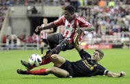 Sunderland's midfielder Stephane Sessegnon (L) is tackled by Liverpool's midfielder Steven Gerrard during the English Premier League football match at The Stadium of Light in Sunderland