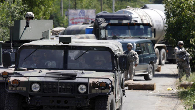U.S. KFOR soldiers in military vehicles patrol past road barricades, in the village Rudare, north of the Serb-dominated part of the ethnically divided town of Kosovska Mitrovica, Kosovo, Wednesday, July 27, 2011. A policeman was seriously wounded after an ambush in Kosovo's north as tensions grow with local Serbs, a police official said Tuesday. The officer was shot and wounded in the head during a firefight near the northern town of Zubin Potok, as the police undertook an operation to extend the authority of the Kosovo government in the Serb-controlled north.(AP Photo/Zveki)