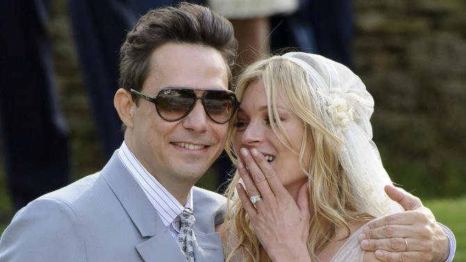 British model Kate Moss and British guitarist Jamie Hince pose for photographers, after their wedding in the village of Southrop, England, Friday, July 1, 2011. (AP Photo/Jonathan Short)