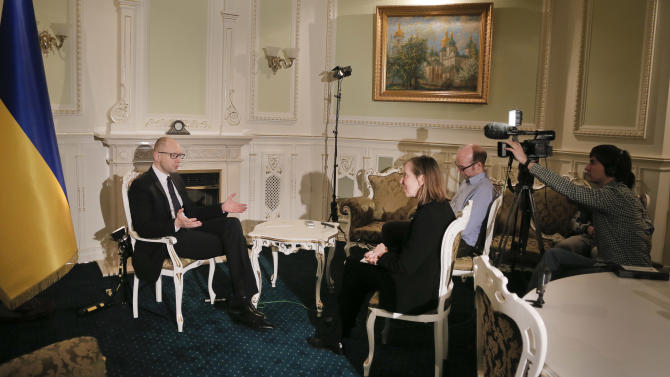 Ukrainian Prime Minister Arseniy Yatsenyuk talks with reporters during an interview with the Associated Press in Kiev, Ukraine, Friday, March 27, 2015.  Yatsenyuk said in an interview with The Associated Press, Friday, that Russia was uninterested in de-escalating Ukraine's conflict with separatist forces, despite a commitment to maintain the peace made in a February cease-fire agreement. (AP Photo/Efrem Lukatsky)