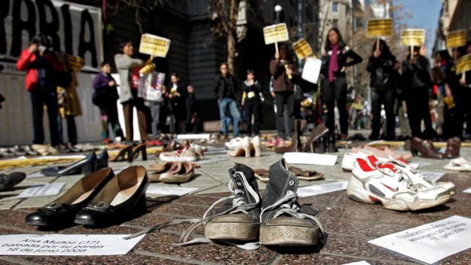 """In this Thursday, July 30, 2009 file photo Shoes representing female victims of violence are displayed by protesters from the Chilean Network Against Domestic and Sexual Violence in Santiago. The sign at bottom reads in Spanish """"Rosa Alvarado, 31, stabbed by ex-boyfriend, 16 April 2008."""" About a third of women worldwide have been physically or sexually assaulted by a former or current partner, according to the first major review of violence against women. In a series of papers released on Thursday June 20, 2013 by the World Health Organization and others, experts estimated nearly 40 percent of women killed worldwide were slain by an intimate partner and that being assaulted by a partner was the most common kind of violence experienced by women. (AP Photo/Santiago Llanquin, File)"""