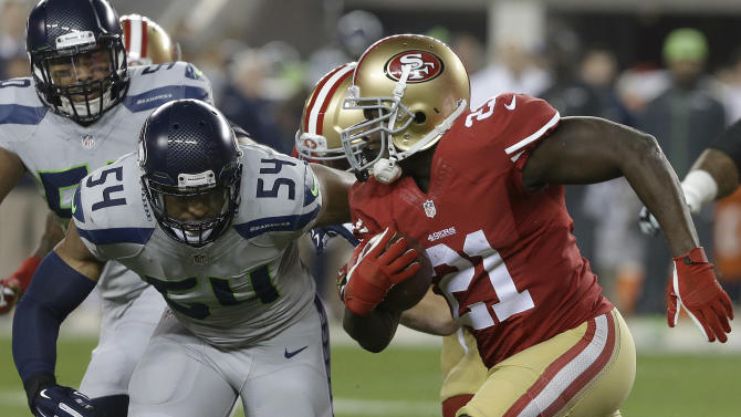 San Francisco 49ers running back Frank Gore (21) runs against Seattle Seahawks middle linebacker Bobby Wagner (54) during the first quarter of an NFL football game in Santa Clara, Calif., Thursday, Nov. 27, 2014