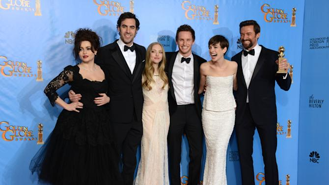 """Actors Helena Bonham Carter, Sacha Baron Cohen, Amanda Seyfried, Eddie Redmayne, Anne Hathaway and Hugh Jackman, from left to right, pose with the award for best motion picture comedy or musical for """"Les Miserables"""" backstage at the 70th Annual Golden Globe Awards at the Beverly Hilton Hotel on Sunday Jan. 13, 2013, in Beverly Hills, Calif. (Photo by Jordan Strauss/Invision/AP)"""