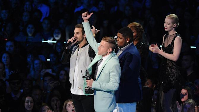 """Ryan Lewis, left, Macklemore, center, and Ray Dalton accept the award for best hip hop video for """"Can't Hold Us"""" as presenters Iggy Azalea, right, and Lil' Kim look on, at the MTV Video Music Awards on Sunday, Aug. 25, 2013, at the Barclays Center in the Brooklyn borough of New York. (Photo by Charles Sykes/Invision/AP)"""