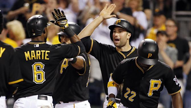 Pittsburgh Pirates' Starling Marte (6) celebrates with Neil Walker, center, as he crosses the plate after hitting a three-run home run off Milwaukee Brewers starting pitcher Kyle Lohse in the fifth  inning of a baseball game in Pittsburgh, Saturday, April 18, 2015. (AP Photo/Gene J. Puskar)