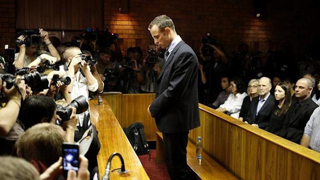 Oscar Pistorius stands at the dock before the start of proceedings at a Pretoria magistrates court (Reuters)