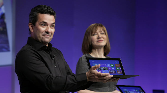Mike Angiulo, corporate vice president of the Planning and PC Ecosystem team at Microsoft, shows the company's Surface tablet computer at the launch of Microsoft Windows 8, in New York,  Thursday, Oct. 25, 2012. Windows 8 is the most dramatic overhaul of the personal computer market's dominant operating system in 17 years. He is accompanied by Microsoft Vice President Julie Larson-Green. (AP Photo/Richard Drew)