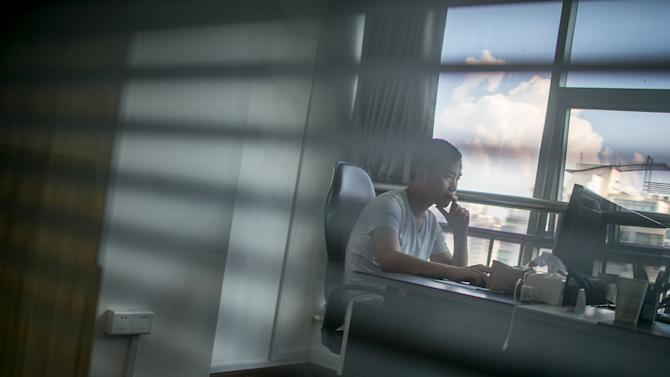 Zhang Xiongjie looks at a computer screen as he works at his office in Hangzhou