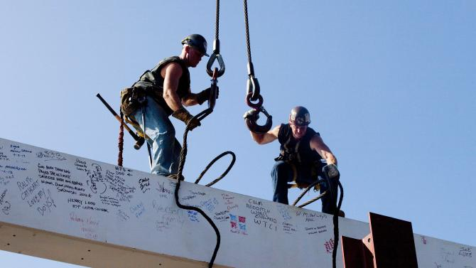 "FILE - In this file photo of Aug. 2, 2012, ironworkers James Brady, left, and Billy Geoghan release the cables from a steel beam after connecting it on the 104th floor of One World Trade Center in New York. The beam was signed by President Barack Obama with the notes: ""We remember,"" ''We rebuild"" and ""We come back stronger!"" during a ceremony at the construction site June 14. Also adorned with the autographs of workers and police officers at the site, the beam will be sealed into the structure of the tower, which is scheduled for completion in 2014. (AP Photo/Mark Lennihan, File)"