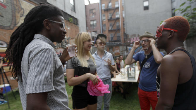 In this Wednesday, July 25 2012 photo, a group of people hang at Timeshare Backyard on the Lower East Side of Manhattan. The city's lone timeshare backyard allows New Yorkers to invite up to 30 guests for two hours at a time and comes with grills, lounge chairs and trashy magazines.  (AP Photo/Mary Altaffer)
