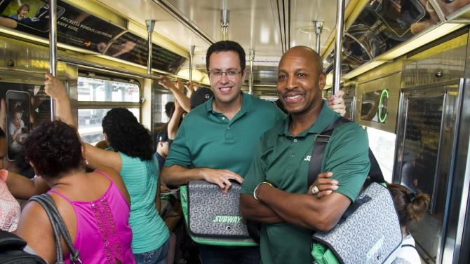 "IMAGE DISTRIBUTED FOR SUBWAY - Baseball all-star Willie Randolph, right, and Jared ""The SUBWAY Guy"" ride the 7 train while giving out the new limited edition SUBWAY bag that encourages healthier lifestyles on Tuesday, July 16, 2013 in New York. (Photo by Charles Sykes/Invision for SUBWAY/AP Images)"