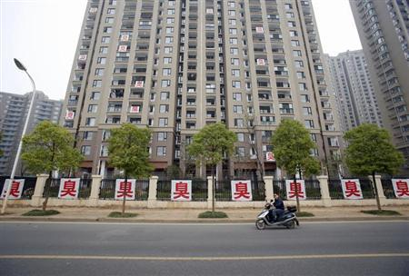 A motorist rides past banners hanging outside a residential community in Wuhan