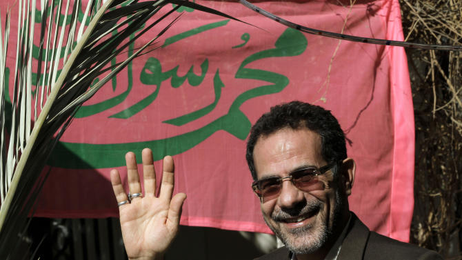 Lawyer Taimoor Karimi is seen outside his home in Muharraq, Bahrain, on Friday, Nov. 9, 2012. Karimi is one of 31 people to have his Bahraini citizenship revoked by the government as part of its crackdown on the opposition. A religious banner behind him praises Islam's founding Prophet Mohamed. (AP Photo/Hasan Jamali)