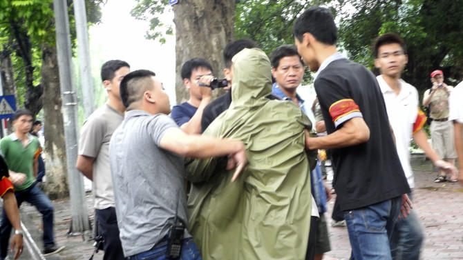 Vietnamese policemen bring a protester, center, after breaking up an anti-China demonstration in Hanoi, Vietnam, Sunday, Aug. 21, 2011. Police arrested dozens of protesters who refused to stop chanting and forcing them onto two buses that were driven away. The Communist government had warned protesters not to gather after allowing peaceful rallies to take place over the past two months. Vietnam and China have been at odds this summer over disputed territory in the South China Sea. (AP Photo/Margie Mason)