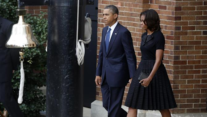 President Barack Obama and first lady Michelle Obama arrive at a memorial service for the victims of the Washington Navy Yard shooting at Marine Barracks Washington Sunday, Sept. 22, 2013.  A gunman killed 12 people in the Navy Yard on Monday, Sept. 16, 2013, before being fatally shot in a gun battle with law enforcement. The president and first lady Michelle Obama also visited with the victims' families. (AP Photo/Charles Dharapak)
