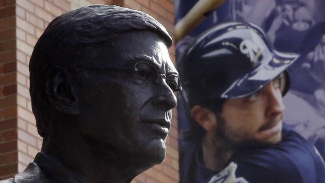 A statue of Major League Baseball Commissioner Bud Selig is displayed outside of Miller Park where a banner showing suspended Milwaukee Brewers star Ryan Braun hangs before a baseball game between the Brewers and the San Diego Padres Tuesday, July 23, 2013, in Milwaukee. (AP Photo/Morry Gash)
