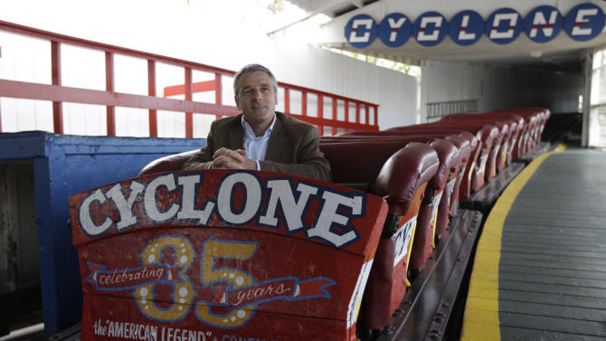 In a Tuesday, June 26, 2012 photo taken on Coney Island in New York,  Valerio Ferrari, President of Central Amusement International, is interviewed while sitting in the one of the Cyclone roller coaster cars.  (AP Photo/Mary Altaffer)