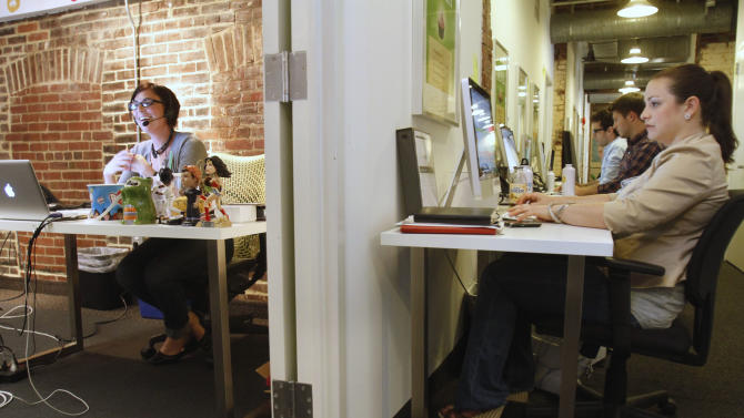 In this April 29, 2011 photo, Leslie Hall, left, works inside an office as and Kelly Bigel, 22, right, and other members of the merchant services department of LivingSocial work in a hallway at LivingSocial's offices in Washington. (AP Photo/Jacquelyn Martin)