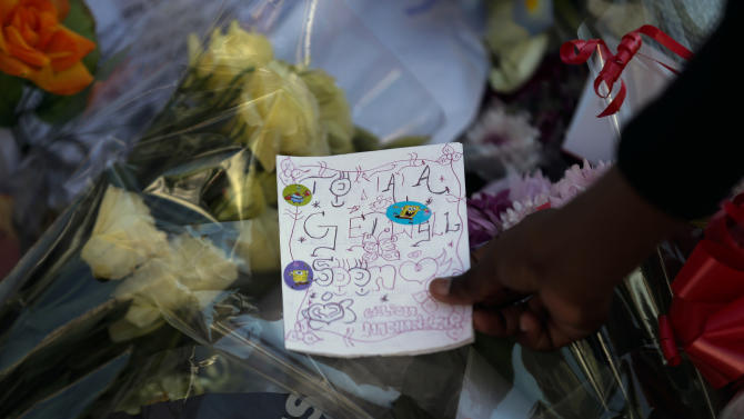 A girl lays down a letter in support of former South African President Nelson Mandela at the entrance of the Mediclinic Heart Hospital where Nelson Mandela is being treated in Pretoria, South Africa, Monday, July 1, 2013. Former president Nelson Mandela remained in a critical condition on Monday. (AP Photo/Markus Schreiber)