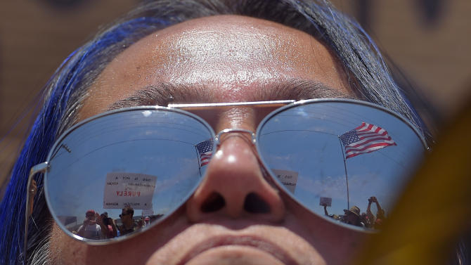 A pro-immigration demonstrator looks across a police line at the opposing side, Friday, July 4, 2014, outside a U.S. Border Patrol station in Murrieta, Calif. Demonstrators on both sides of the immigration debate had gathered where the agency was foiled earlier this week in an attempt to bus in and process some of the immigrants who have flooded the Texas border with Mexico. (AP Photo/Mark J. Terrill)
