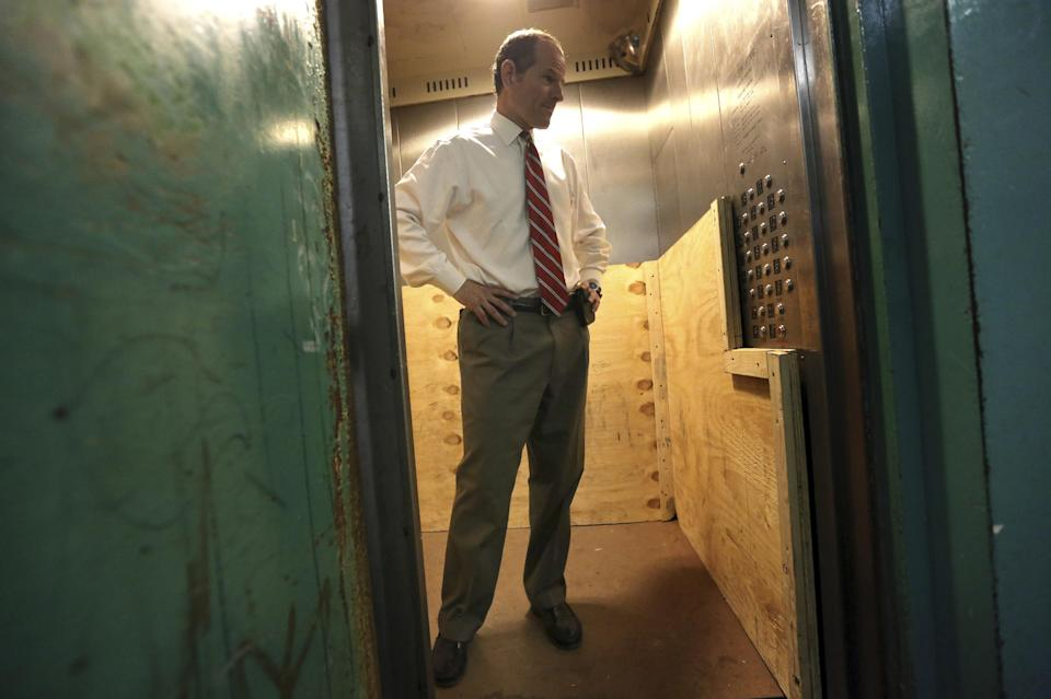 New York City comptroller candidate Eliot Spitzer inspects an elevator as he tours The Frederick Douglass Houses, Wednesday, Aug. 21, 2013 in New York. Spitzer called for sweeping reforms to the public housing system and delivers a sharp rebuke of Mayor Michael Bloomberg's suggestion of fingerprinting tenants. (AP Photo/Mary Altaffer)
