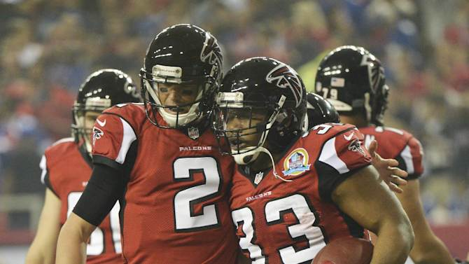 Atlanta Falcons quarterback Matt Ryan (2) reacts with Atlanta Falcons running back Michael Turner (33) after Turner's touchdown run against the New York Giants during the first half of an NFL football game on Sunday, Dec. 16, 2012, in Atlanta. (AP Photo/Rich Addicks)