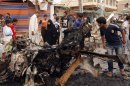 Civilians inspect the scene of a car bomb attack in the Kamaliyah neighborhood, a predominantly Shiite area of eastern Baghdad, Iraq, Monday, May 20, 2013. A wave of car bombings across Baghdads Shiite neighborhoods and in the southern city of Basra killed and wounded scores of people, police said. (AP Photo/ Hadi Mizban)