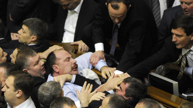 Ukrainian lawmakers fight around the rostrum during the first session of Ukraine's newly elected parliament in Kiev, Ukraine, Thursday, Dec. 13, 2012.  Ukraine's newly elected parliament has chosen a pro-government speaker amid violent brawls between pro-presidential and opposition lawmakers. On Thursday, opposition lawmakers swarmed the parliament's presidium and a fight erupted with pro-government legislators. The opposition demanded that their opponents stop voting in place of their absent colleagues.  (AP Photo/Sergei Chuzavkov)
