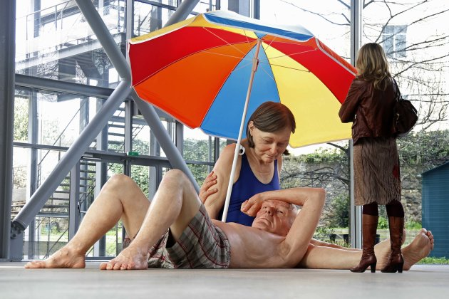 "A visitor looks at a sculpture entitled ""Couple Under an Umbrella, 2013"" by artist Ron Mueck during his exhibition at the Fondation Cartier pour l'art contemporain in Paris"