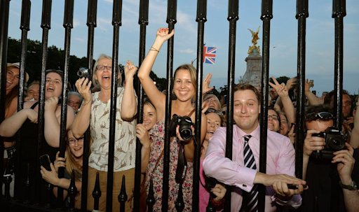 The large waiting crowds cheer on July 22, 2013 at the announcement of the birth of a baby boy, at 4:24 pm to Prince William and Catherine, Duchess of Cambridge, at St Mary's Hospital