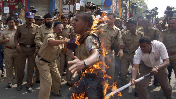 FILE - In this Feb. 20, 2010 file photo, Indian police try to douse fire after student S. Yadaiah set himself on fire during a protest demanding separate Telangana state in Hyderabad, India. Ever since India's ruling coalition endorsed the creation of the new southern state of Telangana, a rash of demands for new states have burst into mutinous life across India, with strikes and protests that could redraw the country's political map. Leaders of the Gorkhaland and Bodo movements, two of the most prominent splinter groups, view the Telangana decision as nothing short of a betrayal of their own dreams. (AP Photo/File)