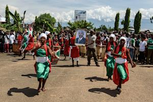 Women dance as people hold a portrait of the Burundian …