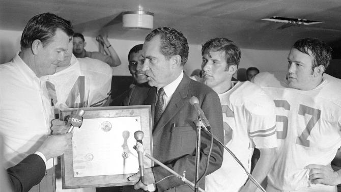 FILE - In this Dec. 6, 1969, file photo, President Richard Nixon presents a plaque to Texas football coach Darrell Royal, proclaiming the Longhorns the No. 1 college football team in college football's 100th year, after their 15-14 win over Arkansas in Fayetteville, Ark. Royal, who won two national championships and turned the Longhorns program into a national power, died early Wednesday, Nov. 7, 2012, at age 88 of complications from cardiovascular disease, school spokesman Bill Little said. Royal also had suffered from Alzheimer's disease. (AP Photo/File)