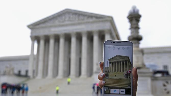 A Supreme Court visitor takes pictures with her cell phone outside the Supreme Court in Washington, Tuesday, April 29, 2014, during a hearing. The Supreme Court is considering whether police may search cellphones found on people they arrest without first getting a warrant. ( AP Photo/Jose Luis Magana)