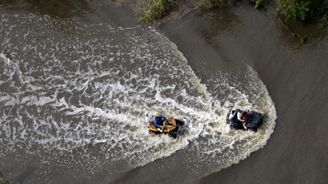 People ride ATV's through flooded streets in Lafitte, La., after Hurricane Isaac came through the region, Thursday, Aug. 30, 2012. (AP Photo/Gerald Herbert)