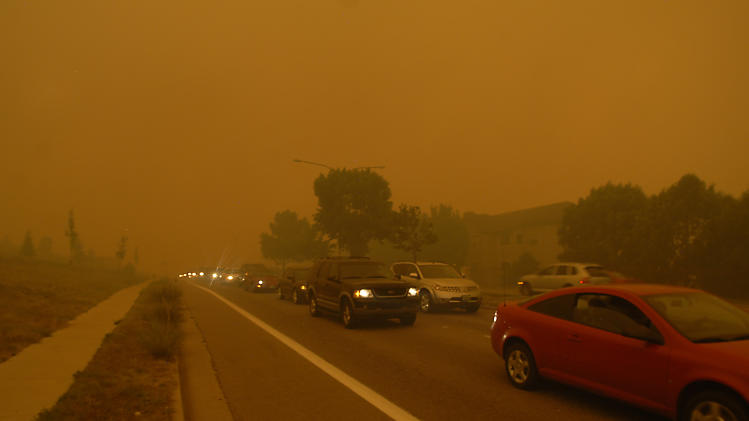People flee the Waldo Canyon Fire with little time to spare as the fire burns through neighborhoods west of Colorado Springs, Colo. on Tuesday, June 26, 2012. The blaze left a trail of destruction, burning homes and buildings in it's path. Heavily populated areas in the fire's path have been affected. (AP Photo/Bryan Oller)