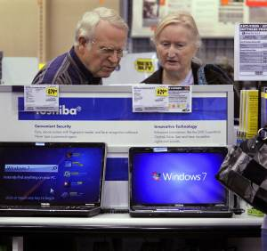 FILE -In this Thursday, Oct. 22, 2009, file photo, computer shoppers read through options and compare prices at a Best Buy in Springfield, Ill., after Microsoft launched Windows 7. Best Buy is hoping to capitalize on the launch of Windows 8. It's trying to lure customers with exclusive computers and staffers trained to explain and demonstrate the new operating system from Microsoft Corp. (AP Photo/Seth Perlman, File)