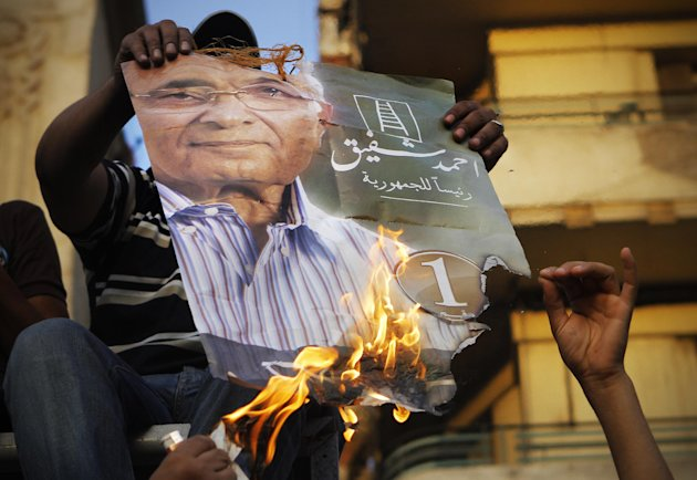 "Muslim brotherhood's presidential candidate Mohammed Morsi supporters burn a poster for presidential candidate Ahmed Shafiq, in Tahrir Square, the focal point of Egyptian uprising, in Cairo, Egypt, Tuesday, June 19, 2012. The Brotherhood has called for mass demonstrations in Cairo and elsewhere on Tuesday to protest the interim charter issued by the military as well as a court ruling last week that dissolved parliament, where the Brotherhood controlled nearly half the seats. Already, several thousand protesters have gathered in Cairo's Tahrir Square, birthplace of the uprising that toppled Mubarak 16 months ago. Arabic on the poster reads, ""Ahmed Shafiq for Egyptian presidency."" (AP Photo/Amr Nabil)"