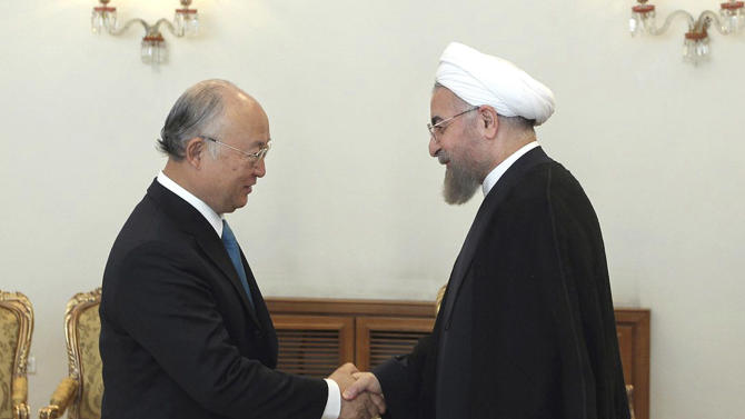 In this photo released by the official website of the office of the Iranian Presidency, Iran's President Hassan Rouhani, right, shakes hands with Director General of the International Atomic Energy Agency Yukiya Amano at the start of their meeting in Tehran, Iran, Sunday, Aug. 17, 2014. (AP Photo/Mohammad Berno, Iranian Presidency Office)