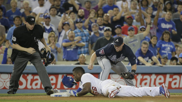 Los Angeles Dodgers' Yasiel Puig, bottom, safely takes third base after hitting a triple as Atlanta Braves third baseman Chris Johnson watches during the fifth inning of a baseball game on Tuesday, July 29, 2014, in Los Angeles. (AP Photo/Jae C. Hong)