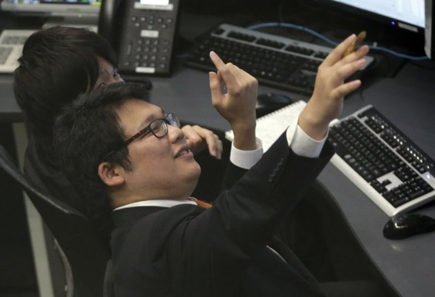 Employees of the Tokyo Stock Exchange look at an electric stock quotation board at the bourse in Tokyo